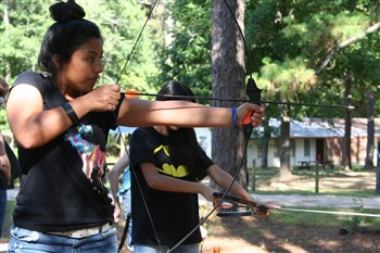 A camper at Centenary Camp tries her hand at archery