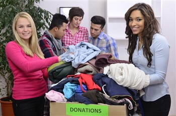 Young volunteers of different ethnicity sort clothes from a donation box