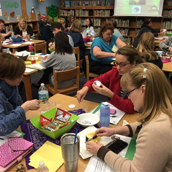 Teachers at elementary school media center at tables preparing civility kits