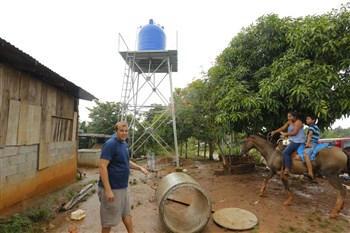 Blake Davidson of Agua Viva Serves in front of a well and apparatus