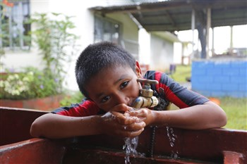 Boy from Costa Rica drinking from outdoor tap