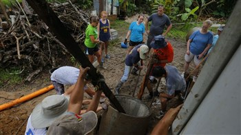 Mission team members from First UMC, Winter Park, help install a septic tank