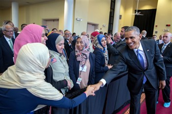 President Barack Obama shaking hands with someone in head covering in a line of others
