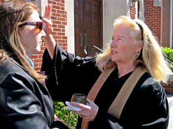 Rev. Vicki Walker, right, administers ashes on the forehead of Lynn Osborne outside Portico chapel