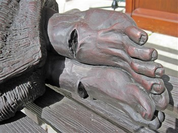 Close-up of sculpted feet with telltale nail holes on Homeless Jesus statue