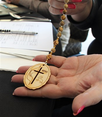 General Conference listening session participants check out a prayer bead medallion for the 2016 event