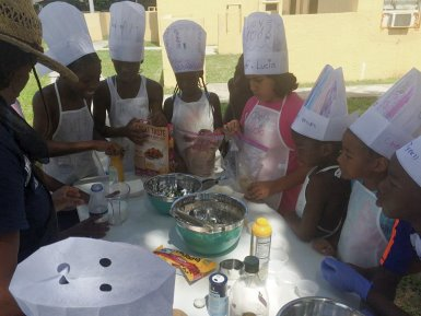 Group of children wearing chef hats as they learn summer meal prep skills around a table.